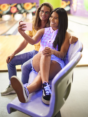Buy stock photo Shot of a beautiful young couple taking a selfie while on a date in a bowling alley