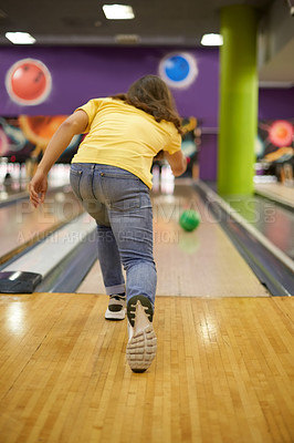 Buy stock photo Rearview shot of an unrecognizable man bowling in a bowling alley