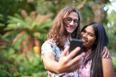 Buy stock photo Cropped shot of a beautiful young couple taking a selfie while on a date in nature
