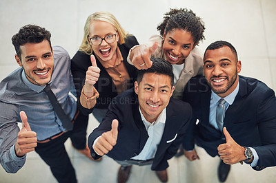 Buy stock photo High angle portrait of a group of cheerful young businesspeople showing thumbs up in the air while standing in the office during the day