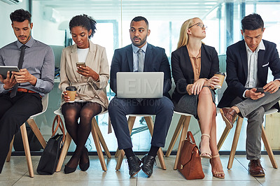 Buy stock photo Shot of a group of focussed young businesspeople seated together on chairs and making notes using different methods while waiting in the office during the day