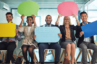 Buy stock photo Portrait of a group of cheerful young businesspeople seated together on chairs while holding up signs inside of the office during the day