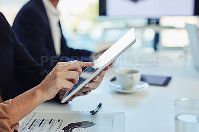 Buy stock photo Cropped shot of a businesswoman using a digital tablet during a meeting in the boardroom of a modern office