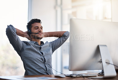 Buy stock photo Shot of a young call centre agent taking a break while working in an office