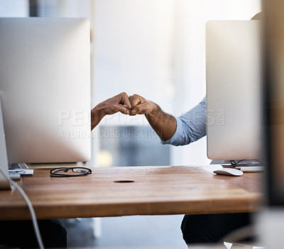 Buy stock photo Shot of two unrecognizable businessmen fist bumping in an office