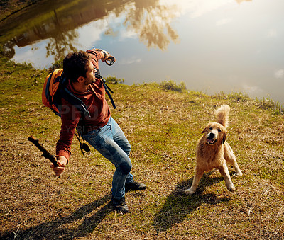 Buy stock photo Full length shot of a handsome young man playing fetch with his dog by a lake in the park