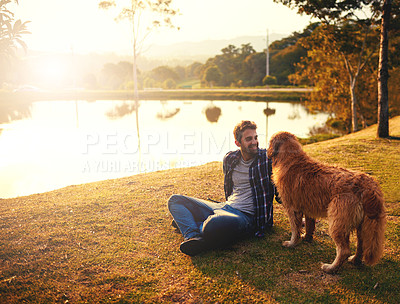 Buy stock photo Full length shot of a handsome young man and his dog spending a day by a lake in the park