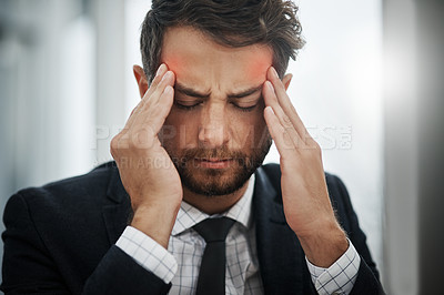 Buy stock photo Shot of a young businessman suffering with a headache in an office