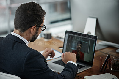 Buy stock photo Shot of a young businessman making a video call on a laptop in an office