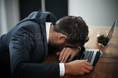 Buy stock photo Shot of a young businessman lying with his head down on a laptop in an office