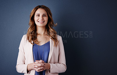 Buy stock photo Studio portrait of an attractive and confident young businesswoman posing against a dark blue background