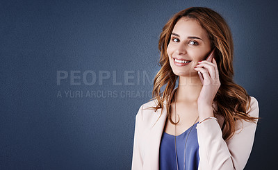Buy stock photo Studio portrait of an attractive young businesswoman using a mobile phone against a dark blue background
