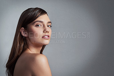 Buy stock photo Studio portrait of a beautiful young woman posing against a gray background