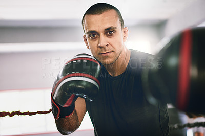 Buy stock photo Portrait of a confident young male boxer wearing boxing gloves while throwing punches at the camera inside of a ring at a gym during the day