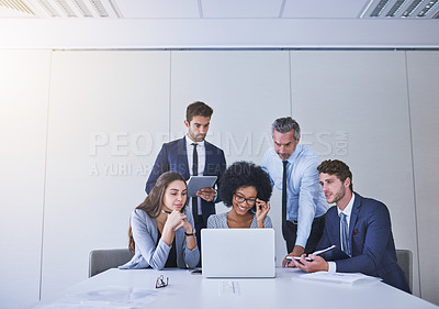 Buy stock photo Shot of a diverse group of businesspeople working together on a laptop in an office