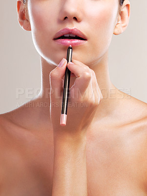 Buy stock photo Studio shot of a beautiful young woman applying lip liner against a beige background