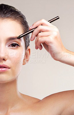 Buy stock photo Studio shot of a beautiful young woman applying eyeliner against a beige background