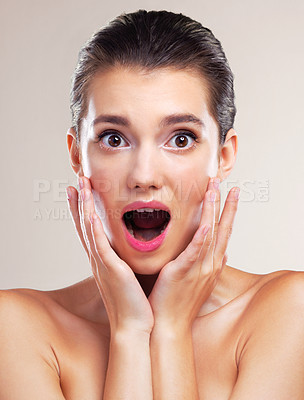Buy stock photo Studio portrait of a beautiful young woman looking scared against a beige background