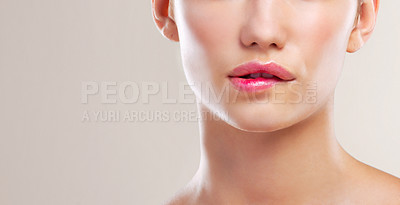 Buy stock photo Cropped studio shot of a beautiful young woman biting her lip against a beige background