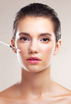 Buy stock photo Studio portrait of a beautiful young woman getting her face injected against a beige background