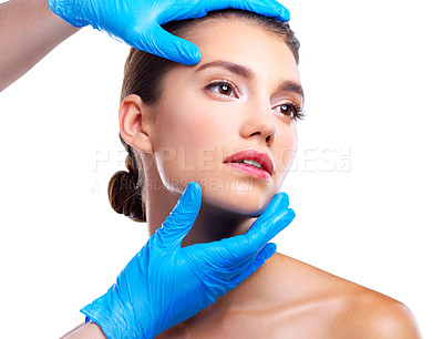 Buy stock photo Studio shot of a beautiful young woman getting her face analyzed by gloved hands against a beige background