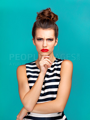 Buy stock photo Studio portrait of a beautiful young woman looking angry against a turquoise background