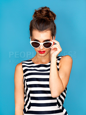Buy stock photo Studio shot of a beautiful young woman wearing glasses while posing against a blue background