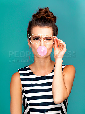 Buy stock photo Studio portrait of a beautiful young woman blowing bubblegum against a turquoise background