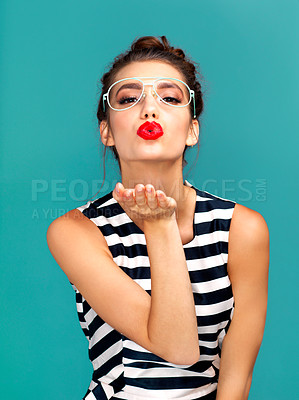 Buy stock photo Studio portrait of a beautiful young woman blowing a kiss against a turquoise background