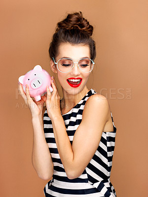 Buy stock photo Studio shot of a beautiful young woman holding a piggybank against a bronze background