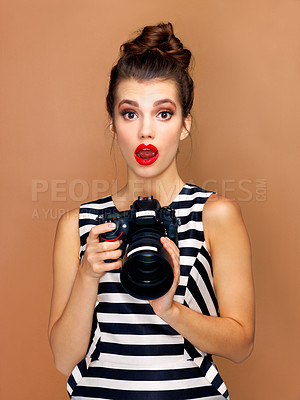 Buy stock photo Studio portrait of a beautiful young woman taking a photo with a camera against a bronze background