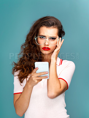 Buy stock photo Studio portrait of a beautiful young woman using a cellphone against a turquoise background