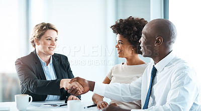 Buy stock photo Shot of a young man and woman shaking hands during a meeting with a financial planner in a modern office