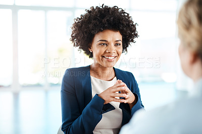 Buy stock photo Shot of two young businesswomen having a discussion in a modern office