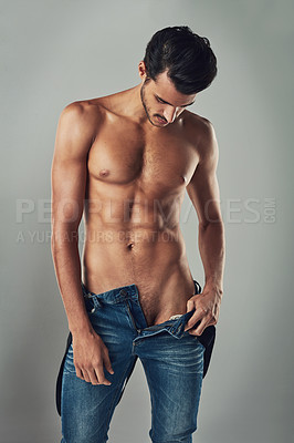 Buy stock photo Studio shot of a handsome and muscular young man taking off his jeans against a grey background