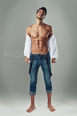 Buy stock photo Studio shot of a handsome young man showing off his muscular body against a grey background