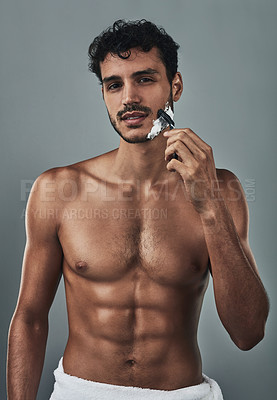 Buy stock photo Studio shot of a handsome and shirtless young man shaving his beard against a grey background
