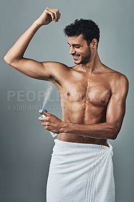 Buy stock photo Studio shot of a handsome young man applying deodorant against a grey background