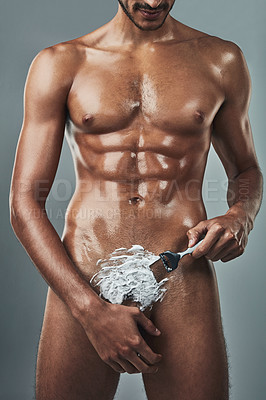Buy stock photo Cropped studio shot of a muscular young man shaving his pubic hair against a grey background