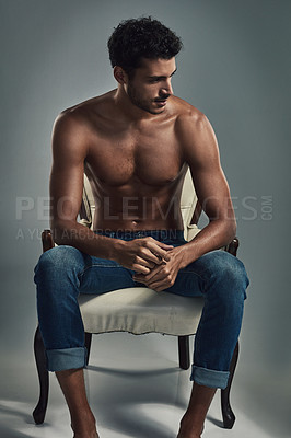 Buy stock photo Studio shot of a handsome and shirtless young man sitting on a chair against a grey background