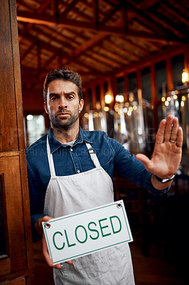 Buy stock photo Portrait of a serious looking young business owner holding up a sign saying