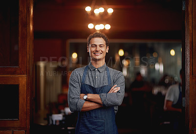 Buy stock photo Shot of a confident young business owner standing with his arms folded under a doorway at a beer brewery during the day