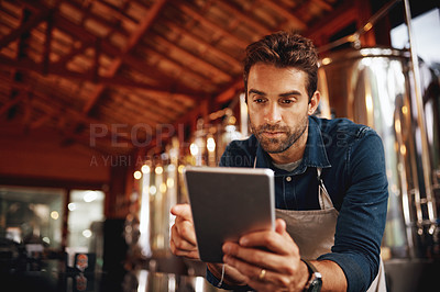 Buy stock photo Shot of a focused young barman browsing on a digital tablet while patiently waiting at the bar for customers inside of a beer brewery during the day