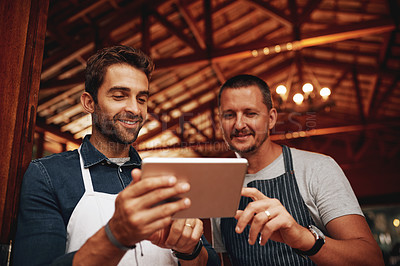 Buy stock photo Shot of two young business owners browsing on a digital tablet at a beer brewery during the day