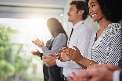 Buy stock photo Shot of a group of young businesspeople standing in a line and applauding in a modern office