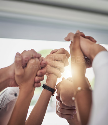 Buy stock photo Cropped shot of a group of businesspeople holding their hands in solidarity