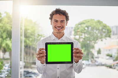 Buy stock photo Portrait of a handsome young businessman holding a digital tablet with a green screen in a modern office