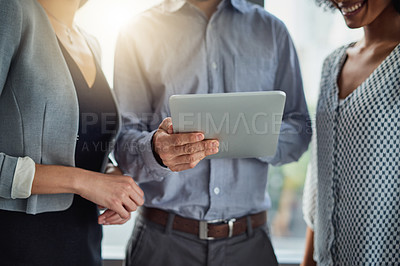 Buy stock photo Cropped shot of a group of businesspeople using a digital tablet together in a modern office