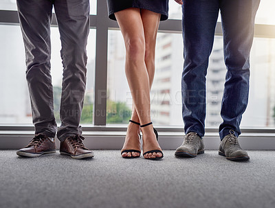 Buy stock photo Cropped shot of a group of unrecognizable businesspeople standing in line in a modern office