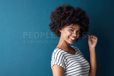 Buy stock photo Studio portrait of an attractive young woman posing against a blue background
